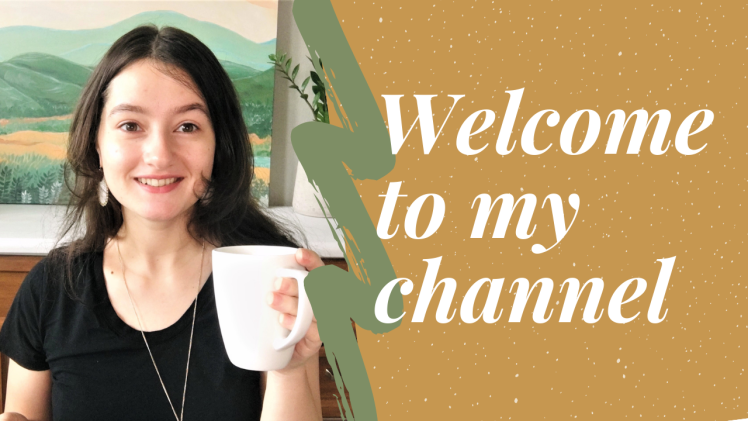 """Picture of me holding a mug, I'm wearing a black shirt and am smiling brightly at the camera. The image has the words overlaid, """"Welcome to my Youtube channel""""."""